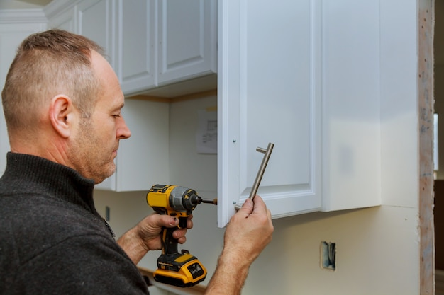 Installation of door handles on kitchen cabinets with a screwdriver Premium Photo