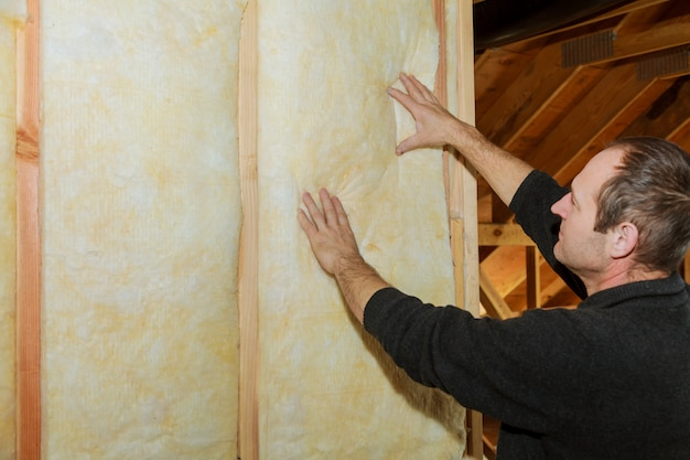 Installation of inside wall insulation in wooden house, building under construction Premium Photo