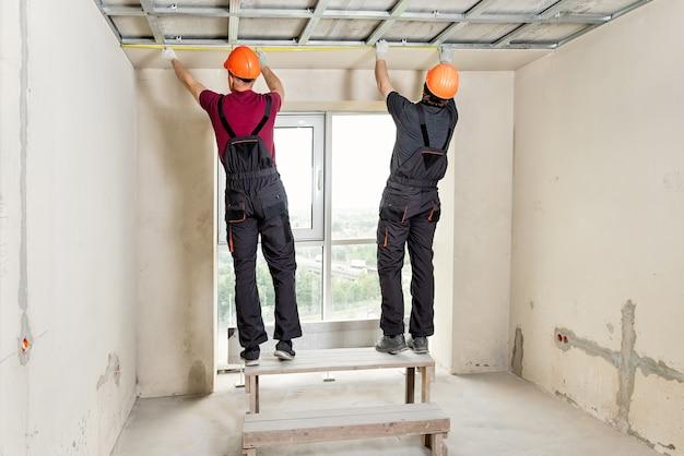 Монтаж гипсокартона. рабочие измеряют потолок. Premium Фотографии