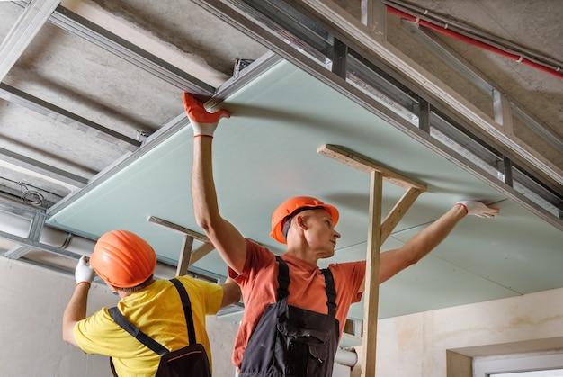 Монтаж гипсокартона. рабочие монтируют гипсокартон к потолку. Premium Фотографии