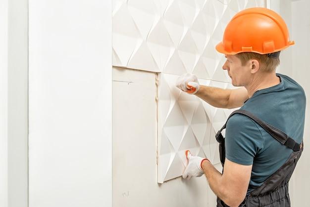 Монтаж гипсовой 3d панели. рабочий прикрепляет гипсовую плитку к стене. Premium Фотографии
