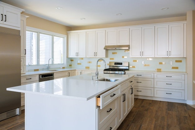 Installing cabinets and counter top a white kitchen partially installed furniture. Premium Photo