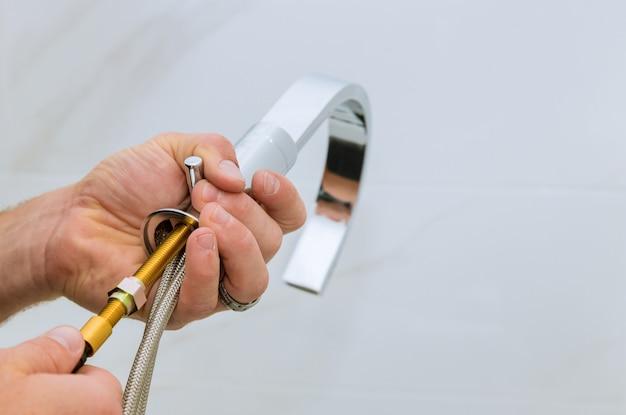 浴室の仕事で浴室の配管工に蛇口を取り付ける Premium写真