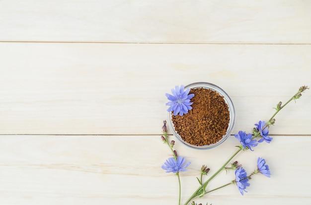 Быстро сублимированные гранулы из корня цикория на светлом деревянном столе. свежие синие цветы cichorium intybus. натуральный заменитель кофе. Premium Фотографии