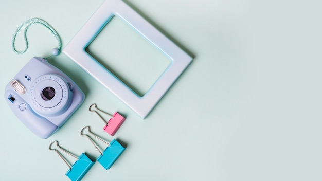 Instant mini camera; paper clips and frame on colored background Free Photo