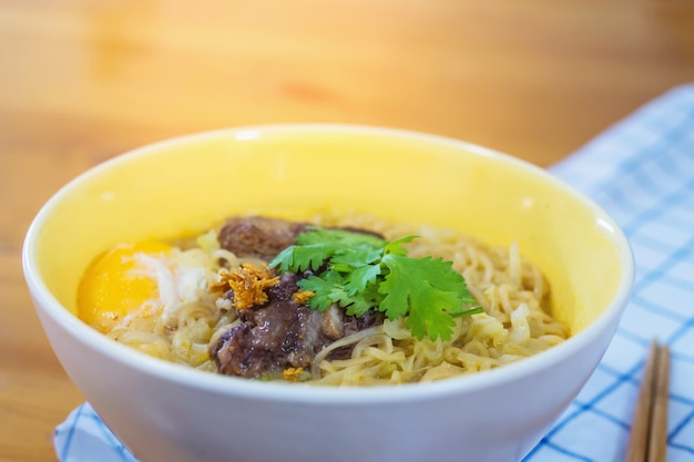 Instant noodle with pork and egg ready to be eaten - delicious instant food menu concept Free Photo