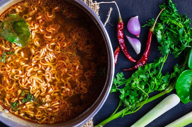 Instant noodles in spicy pot with spices and vegetables. Premium Photo