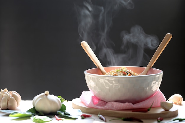 Instant noodles and spoon with wooden fork in cup with smoke rising and garlic Premium Photo