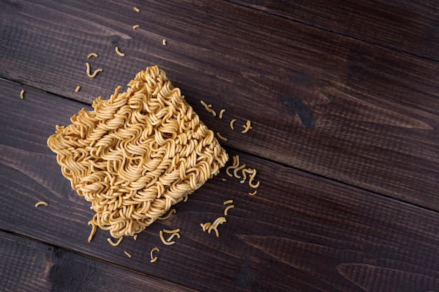 Instant noodles in top view closeup on wooden table with copy space Premium Photo