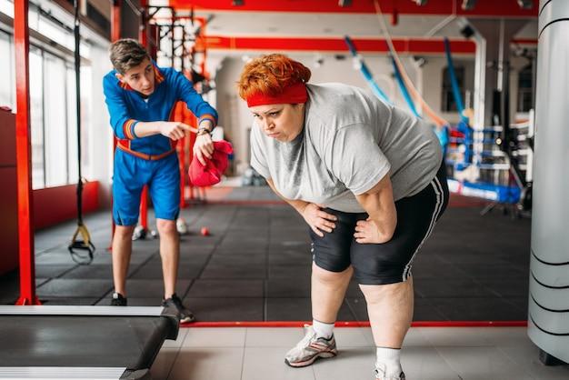 강사 강제로 뚱뚱한 여자 체육관에서 운동 프리미엄 사진