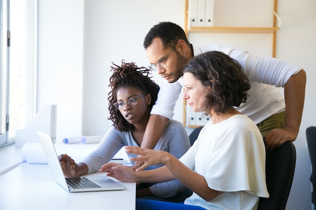 Instructor helping new employees with corporate software Free Photo
