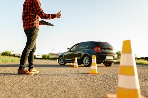 インストラクターは、女子学生が自動車学校のレッスンであるコーンの間をドライブするのを手伝います。 Premium写真