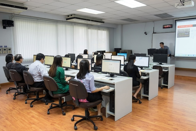 Instructor teaching software using students at computer room. Premium Photo