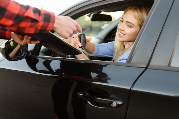 Instructor with checklist gives the keys to student in car, examination or lesson in driving school Premium Photo