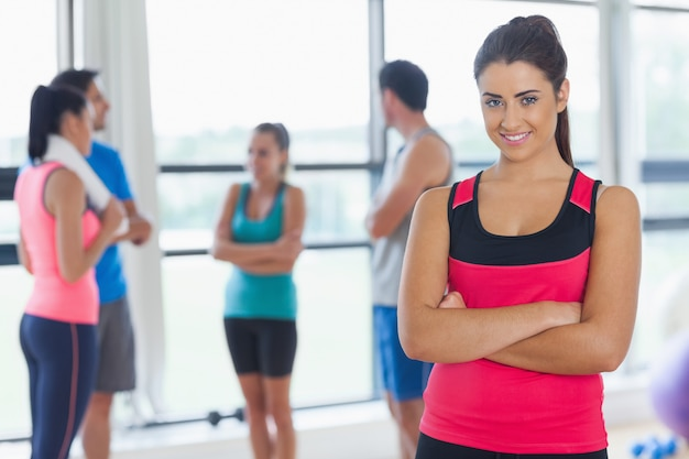 Instructor with fitness class in background in fitness studio Premium Photo
