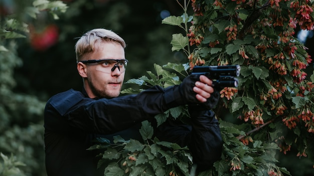 Instructor with gun in forest leads aiming and posing Premium Photo