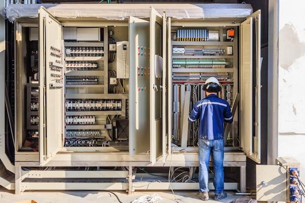 Instrument technician on the job check wiring on plc cabinet Premium Photo