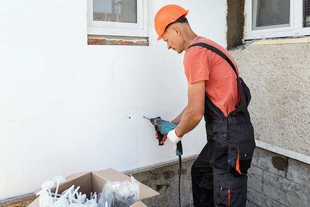 Утепление дома пенопластом. рабочий сверлит отверстия для крепления пенополистирола на фасаде. Premium Фотографии