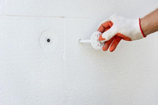 Утепление дома пенопластом. рабочий фиксирует пенополистироловую доску пластиковыми дюбелями. Premium Фотографии