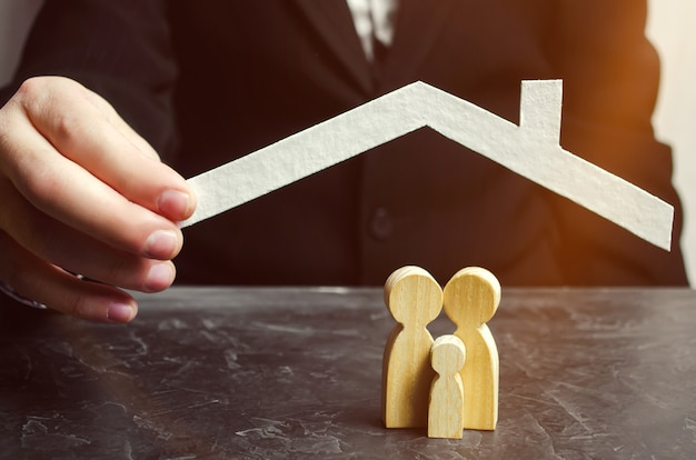Insurance agent holds a house over the family. the concept of insurance of family life and property. Premium Photo