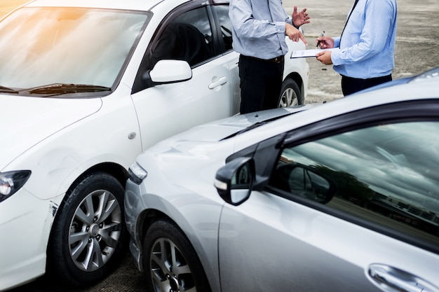 Insurance agent writing on clipboard while examining car after accident Premium Photo