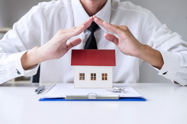 Insurance and care protection of house concept, businessman agent with protective gesture Premium Photo