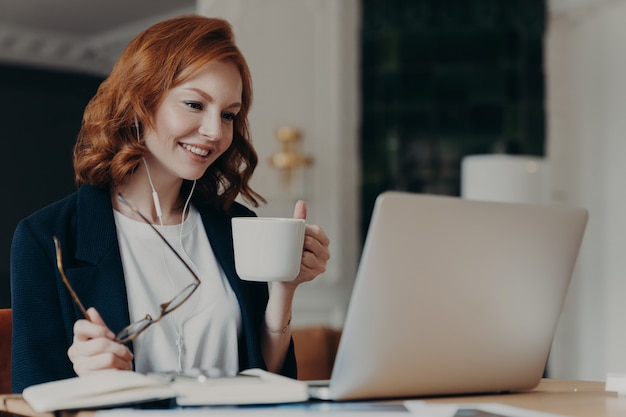 Intelligent female student has online course, concentrated in screen of laptop computer Premium Photo