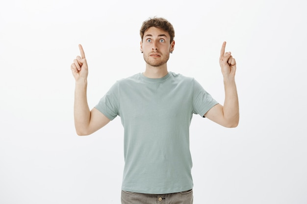 Intense afraid european guy with fair hair, pointing upwards with raised index fingers and staring aside on something scary and shocking Free Photo