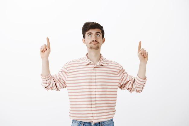 Uomo europeo attraente dispiaciuto intenso con la barba, guardando e rivolto verso l'alto con espressione delusa, essendo impressionato dal lavoro di riparazione in camera, in piedi Foto Gratuite