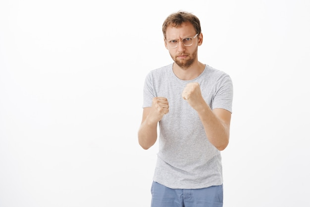 攻撃から身を守るために拳を上げて眉をひそめている眼鏡をかけた剛毛の激しい深刻な怒っている男性 無料写真