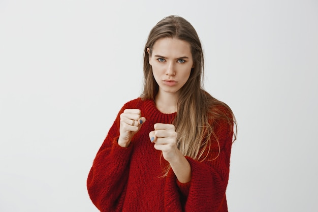 Intense serious woman ready to fight for love. focused good-looking european female model in stylish red loose sweater, standing in boxing pose with raised clenched fists, frowning, ready to defense Free Photo