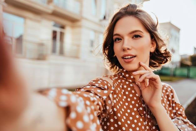 セルフィーを作る茶色の服装で興味を持った魅力的な女性。街を歩きながら自分の写真を撮る壮大なブルネットの女の子。 無料写真