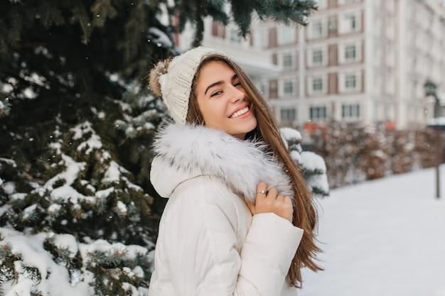 Donna dai capelli lunghi interessata in abbigliamento bianco che gode del periodo invernale felice e che ride. outdoor ritratto di magnifica donna europea in cappello lavorato a maglia in piedi in strada innevata Foto Gratuite