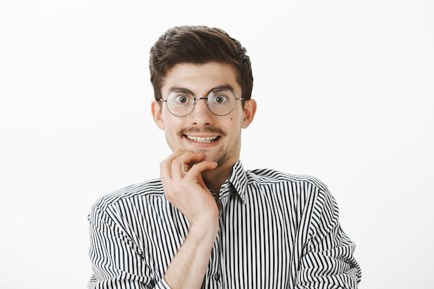 Responsabile di ufficio nerd interessato che guarda con tentazione attraverso gli occhiali al nuovo computer in negozio, sorride nervosamente, desidera acquistare un nuovo gadget, in piedi impaziente e felice sul muro grigio Foto Gratuite