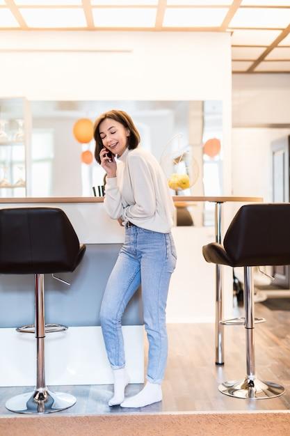Заинтересованная женщина с телефоном стоит в панорамной кухне в повседневной одежде Бесплатные Фотографии