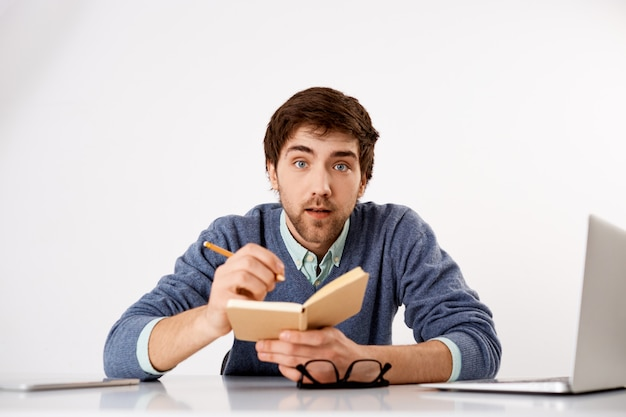 Interested young bearded guy, learn new language online courses while sit home self-quarantine, writing down in notebook, look interested Free Photo