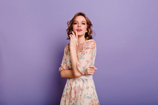 カメラに向かって花柄のライトドレスに興味のある若い女性 無料写真