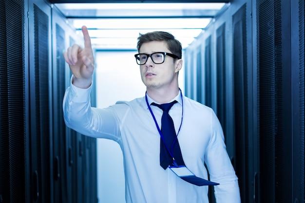 面白い仕事。データセンターで働いて、彼の指で指しているハンサムな触発された男 Premium写真
