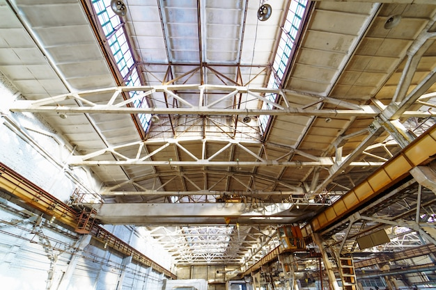 Interior of a big industrial building or factory with steel constructions. the roof inside of new large and modern warehouse space. Premium Photo