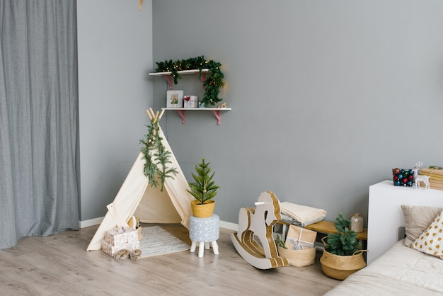 The interior of the children's room, decorated for christmas and new year. wigwam, rocking horse, christmas tree. Premium Photo