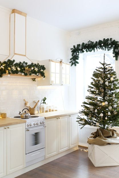 Premium Photo Interior Of A Christmas Light Kitchen Decorated With A Christmas Tree And Garlands