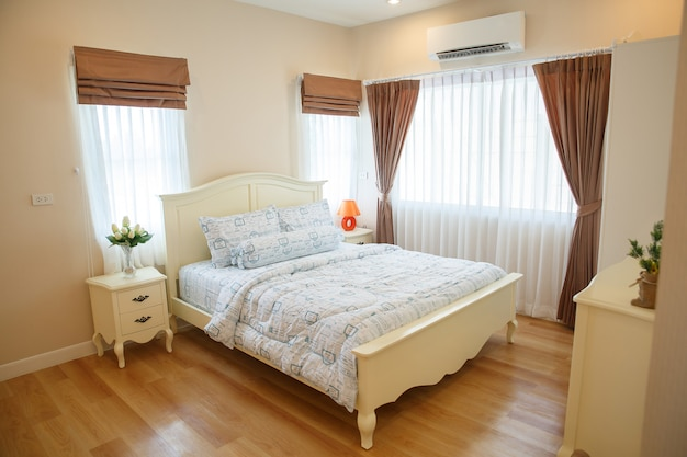 Interior of cozy bedroom in modern design with vase on white wood table. Premium Photo