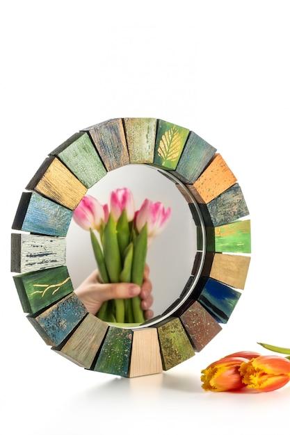 Interior design mirror handmade in wooden frame with bouquet of spring tulips Premium Photo