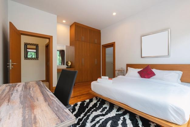 家、家、別荘のインテリアデザインには、ベッド、羽毛布団、敷物、枕、寝室の窓があります。 Premium写真