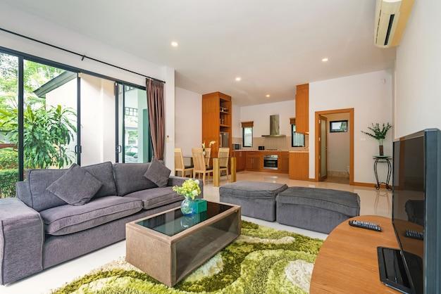家、家、別荘のインテリアデザインには、ソファ、リビングルームのテレビ、ダイニングテーブルがあります。 Premium写真