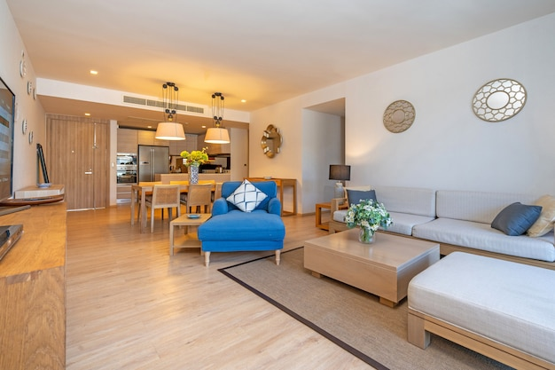 Interior design in villa, house, home, condo and apartment feature living room with television, middle table, cushion and open space kitchen and dining room Premium Photo