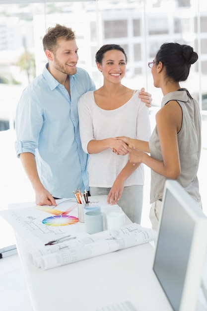 Interior designer shaking hands with smiling client photo - Clients looking for interior designers ...