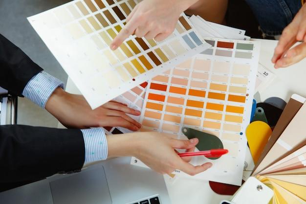 젊은 부부와 함께 작업하는 인테리어 디자이너. 사랑스러운 가족 및 전문 디자이너 또는 건축가가 미래의 인테리어 개념을 논의하고 색상 팔레트, 현대 사무실의 방 도면 작업. 무료 사진