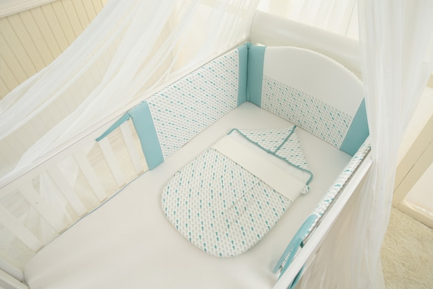Interior of light cozy baby room with crib and bedding Premium Photo