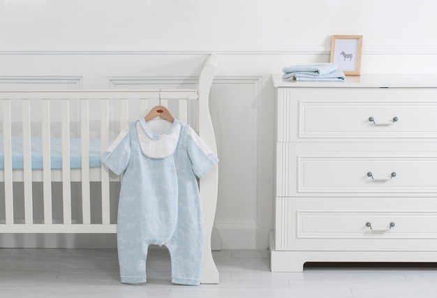 Interior of light cozy baby room with crib and bedding Premium Photo